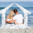 Affectionate couple sitting on the sand — Stock Photo #62491007