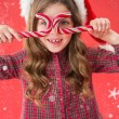 Girl in santa hat holding candy canes — Stock Photo #62491017