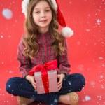 Girl in santa hat holding gift — Stock Photo #62491231