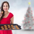 Composite image of happy brunette eating hot cookies — Stock Photo #62492399