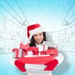 Smiling brunette in santa hat holding stack — Stock Photo #62494435