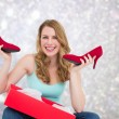 Composite image of smiling woman holding up her new shoes — Stock Photo #62494823