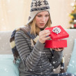 Blond woman opening a gift sitting on a sofa — Stock Photo #62495855