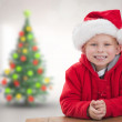 Composite image of cute boy in santa hat — Stock Photo #62495883