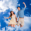 Cheerful young couple jumping — Stock Photo #62497865