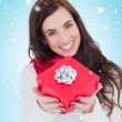 Brunette showing red gift with bow — Stock Photo #62497971