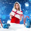 Pretty santa girl holding gift — Stock Photo #62498681