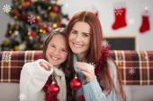 Mother and daughter holding baubles — Stock Photo
