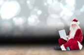 Santa sits and uses a laptop — Photo