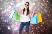 Composite image of cheerful brunette holding shopping bags — Zdjęcie stockowe