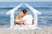 Affectionate couple sitting on the sand — Stock Photo