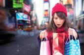 Shocked brunette opening gift bag — Stock fotografie