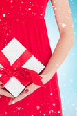 Woman in red dress holding gift — Stock Photo