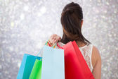 Composite image of rear view of brunette holding shopping bags — Foto de Stock