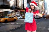 Festive brunette holding gift — Stockfoto