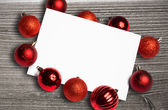 Composite image of red christmas baubles surrounding white page — Foto Stock