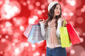 Composite image of thoughtful brunette with shopping bags — Stock Photo