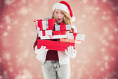 Blonde woman in trouble holding pile of gifts — Stock Photo