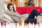 Smiling brunette relaxing on the couch — Stock Photo