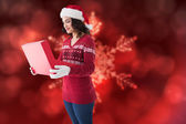 Festive brunette in winter clothes opening gift — Stock Photo