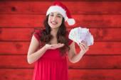 Composite image of festive brunette presenting her cash  — Foto de Stock
