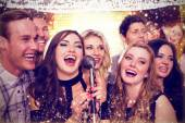 Composite image of friends singing karaoke — Stock Photo