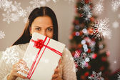 Pretty brunette holding christmas present — Stock Photo