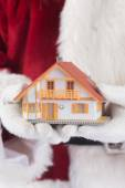 Santa holds tiny house in hands — Stock Photo
