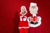 Composite image of santa and mrs claus smiling at camera offerin — Stock Photo