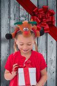 Composite image of cute little girl wearing rudolph headband — Stock Photo