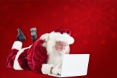 Santa lies in front of laptop — Stock Photo