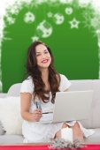 Composite image of smiling woman with laptop and card — Stock Photo