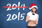 Festive fit brunette holding a weighing scale — Stock Photo