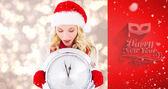 Happy festive blonde with clock — Stock Photo