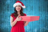 Composite image of festive brunette holding red box — Stock Photo