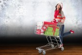 Festive brunette pushing trolley full of gift — Foto de Stock