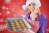 Composite image of festive blonde showing hot cookies — Stock Photo