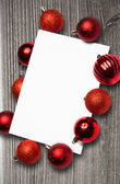 Composite image of red christmas baubles surrounding white page — Stock Photo