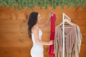 Composite image of woman choosing clothes — Stock Photo