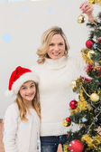 Festive mother and daughter decorating christmas tree — Stock Photo