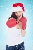Festive brunette in boxing gloves punching — Stock Photo