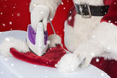 Father Christmas is ironing his hat — Stockfoto