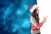 Composite image of smiling brunette in santa hat pointing white  — Stock Photo