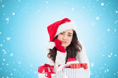 Unsure brunette in santa hat packing gifts — Stock Photo