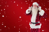 Santa Claus enjoys some music — Stock Photo