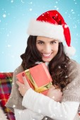 Festive brunette holding gift — Stock Photo