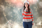 Composite image of festive brunette in santa hat keeping a secre — Stock Photo