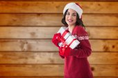 Composite image of cheerful brunette holding christmas presents — Zdjęcie stockowe