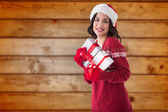 Composite image of cheerful brunette holding christmas presents — Foto de Stock