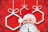 Composite image of festive blonde holding a clock — Photo
